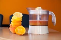 Stapel von frisch zusammengedrückten Zitrusfrüchten nahe bei einem Juicer voll des Safts Stockfoto