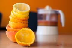 Stapel von frisch zusammengedrückten Zitrusfrüchten und zusammengedrückte Orange in der Front und Juicer voll des Safts im Hinter Lizenzfreies Stockbild