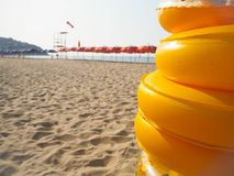 Stapel von gelben aufblasbaren Gummikreisen auf einem einsamen Strand Lizenzfreie Stockfotografie