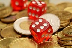 Stapel von goldenen Münzen mit roten Würfeln Stockfoto