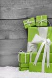 Stapel von grünen Weihnachtsgeschenken, mit Schnee auf Grau  Lizenzfreies Stockbild