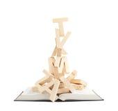 Stapel von hölzernen Buchstaben über dem Buch Stockbilder