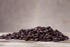 Stapel von Kaffeebohnen auf Holztisch gegenüber von einer defocused Leinwand Lizenzfreie Stockfotografie