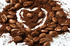 Stapel von Kaffeebohnen und von Kaffeepulver mit Form des Herzens und des Gesichtes stockfotografie