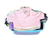 Stapel von Kleidung im Korb auf weißem Hintergrund Stockfotografie