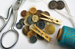 Stapel von Knöpfen mit nähenden Materialien und den Kleidungs-Stiften lokalisiert Stockbild