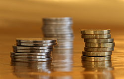 Stapel von Münzen, goldener Hintergrund Stockbilder