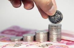Stapel von Münzen und von menschlicher Hand Stockbild