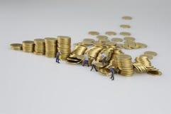 Stapel von Münzen und von Miniaturleuten stockfoto