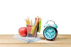 Stapel von Notizbüchern mit Apfel und von Bleistiften im Korbbehälter mit grünem Hefter und Wecker auf Holztisch lizenzfreie stockbilder
