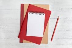 Stapel von Notizbüchern und von roten Bleistift auf einem weißen hölzernen Hintergrund Flache Lage mit Kopienraum stockfotos