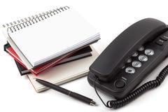 Stapel von Notizbüchern und von schwarzem Telefon Stockbild