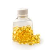 Stapel von Omega 3 Fischölkapseln, die aus einer Flasche heraus verschüttet werden Stockbilder