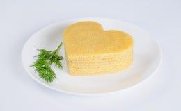 Stapel von Pfannkuchen in Form eines Herzens auf Platte mit Zweig von Stockfoto