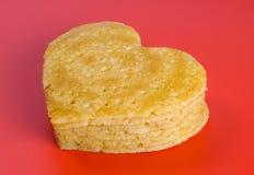 Stapel von Pfannkuchen in Form eines Herzens auf Rot Stockfotografie