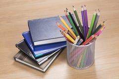 Stapel von Planern mit farbigen Bleistiften im Stand Stockfoto