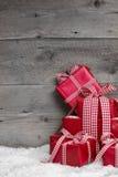 Stapel von roten Weihnachtsgeschenken, Schnee auf grauem hölzernem Hintergrund. Stockfotografie