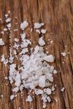 Stapel von Salzkristallen auf dem dunklen hölzernen Hintergrund, Draufsicht, flache Lage, flache Schärfentiefe Stockfoto