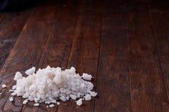Stapel von Salzkristallen auf dem dunklen hölzernen Hintergrund, Draufsicht, flache Lage, flache Schärfentiefe Stockbilder