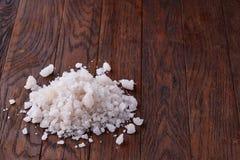 Stapel von Salzkristallen auf dem dunklen hölzernen Hintergrund, Draufsicht, flache Lage, flache Schärfentiefe Stockbild