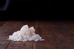 Stapel von Salzkristallen auf dem dunklen hölzernen Hintergrund, Draufsicht, flache Lage, flache Schärfentiefe Lizenzfreies Stockfoto