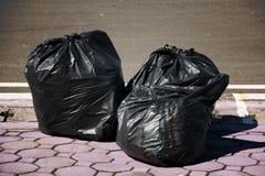 Stapel von schwarzen Abfalltaschen auf der Straße Stockfoto