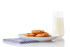 Stapel von selbst gemachten Erdnussbutterplätzchen auf weißer keramischer Platte auf blauer Serviette und Glas Milch Stockfotos