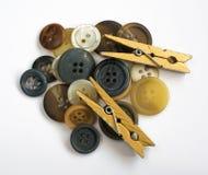 Stapel von sortierten bunten Knöpfen und von hölzernen Kleidungs-Stiften Isolat Lizenzfreies Stockfoto