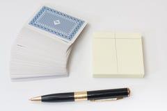 Stapel von Spielkarten mit schwarzem Bleistift und Notizbuch Stockbild