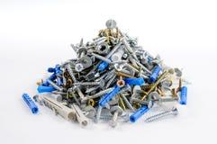 Stapel von Stahl- und Messingschrauben und Plastik- und Metalldübel lyin Lizenzfreies Stockbild