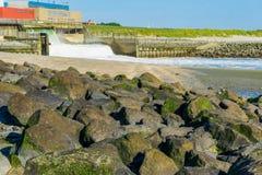 Stapel von Steinen am Strand mit Wasserfallansicht über den Strand Stockbilder