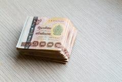 Stapel von tausend thailändischem Geld des Bades auf Holztisch lizenzfreie stockfotografie