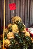 Stapel von ungeschälten Ananas mit Preis am Marktzähler Lizenzfreie Stockbilder