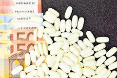 Stapel von Vitaminen und Ergänzungen schließen oben mit Eurorechnungen Stockfoto