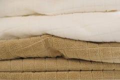 Stapel von Weiß und von Brown-Badetücher-Hintergrund Stockfotografie
