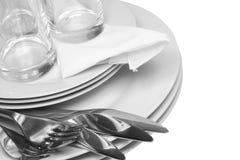 Stapel von weißen Platten, Gläser, Gabeln, Löffel. Lizenzfreie Stockfotos