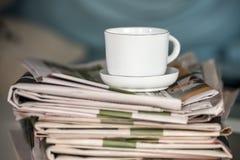 Stapel von Zeitungen und von Kaffeetasse Stockbild
