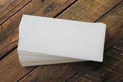 Stapel weiße Umschläge auf einem hölzernen Hintergrund lokalisiert Stockbild