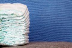 Stapel Windeln oder Windeln auf Blau strickte Hintergrund Lizenzfreie Stockfotografie