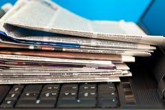 Stapel Zeitungen auf Laptop Stockbild
