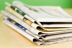 Stapel Zeitungen in der Farbe auf grünem Hintergrund Stockfoto