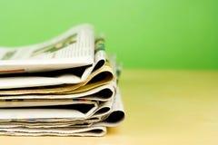 Stapel Zeitungen in der Farbe auf grünem Hintergrund Stockbild