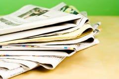 Stapel Zeitungen in der Farbe auf grünem Hintergrund Lizenzfreie Stockfotografie