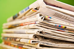 Stapel Zeitungen in der Farbe auf grünem Hintergrund Stockfotografie