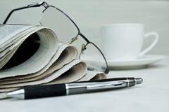 Stapel Zeitungen mit Kaffeetasse auf weißem Hintergrund stockfotografie