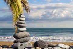 Stapel Zensteine auf Strand mit Palmblättern Stockfotografie