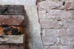 Stapel Ziegelsteine nahe bei teilweise entferntem Wandputz - backgro lizenzfreies stockbild