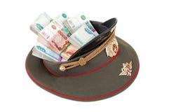 Stapel zusammengerollte Banknoten des russischen Rubels in der Kappe des Offiziers Stockbild
