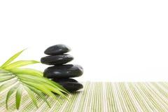 Stapel zwarte basalt in evenwicht brengende stenen met groen blad op bamboemat, op witte achtergrond royalty-vrije stock foto's