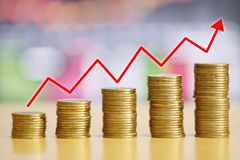 StapelGoldmünze des gewachsenen Finanzkonzeptes und rote Pfeile sind ri stockfoto